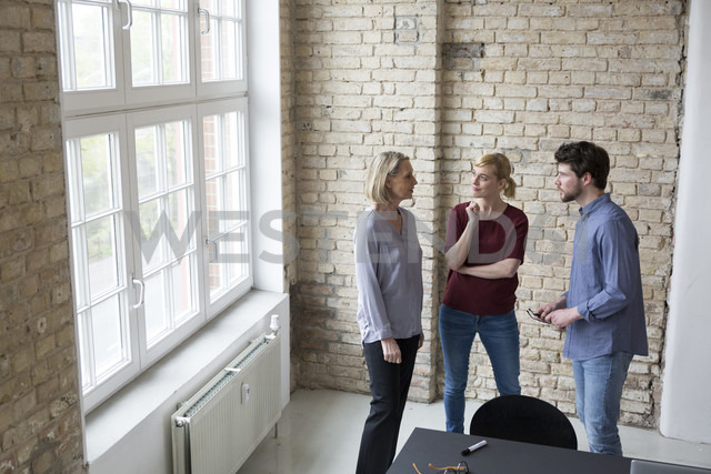 Mature businesswoman working with younger colleagues in office - RBF05767