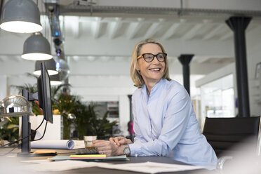 Mature businesswoman working in office, smiling - RBF05773