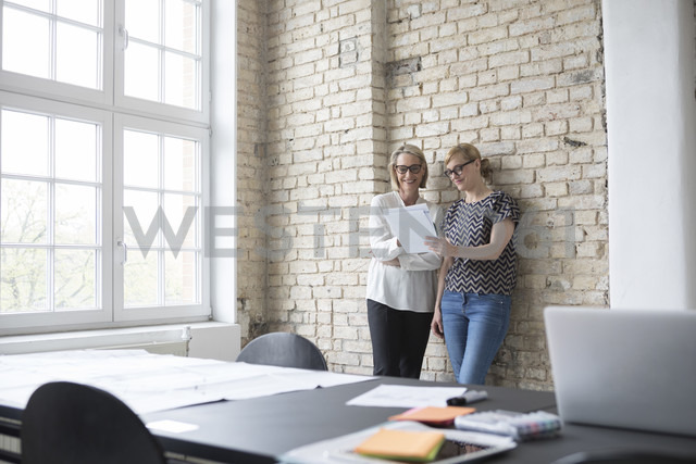 Mature businesswoman working with younger colleague in office - RBF05794