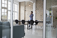 Young entrepreneur standing in his office, thinking - RBF05806