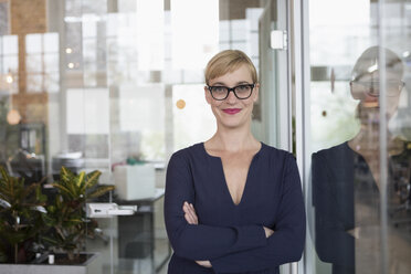 Portrait of a businesswoman in office, holding papers - RBF05824
