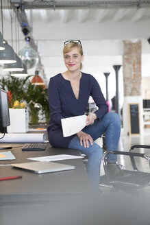 Businesswoman sitting on desk, holding papers - RBF05836
