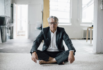 Senior businessman sitting on floor meditating - GUSF00009