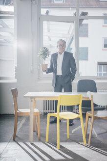 Portrait of senior businessman holding plant - GUSF00036