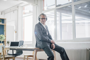 Senior businessman listening to music with headphones in office - GUSF00039