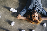 Smiling man lying on the floor surrounded by crumpled paper - KNSF01709
