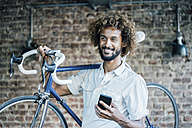 Smiling young man with bicycle and cell phone - KNSF01712