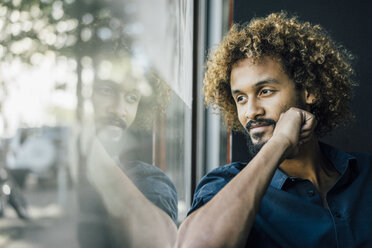 Man with beard and curly hair looking out of window - KNSF01727