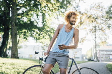 Man with beard and curly hair with bicycle in park - KNSF01730