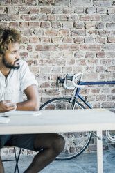 Young man at desk thinking with bicycle in background - KNSF01736