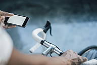 Close-up of man with bicycle checking cell phone - KNSF01745