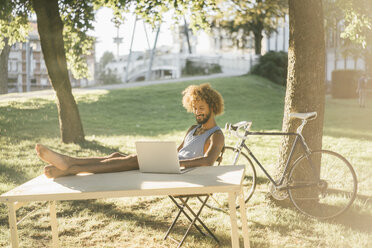 Man with beard and curly hair using laptop at table in park - KNSF01748
