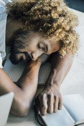 Young man lying on desk sleeping - KNSF01754