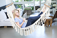 Blond woman with tablet relaxing in hammock in the living room - MAEF12259