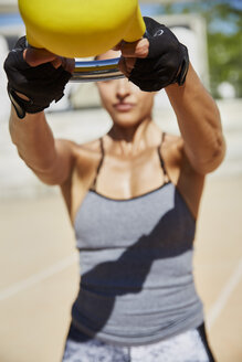 Fit woman exercising with kettlebell outdoors - SUF00183