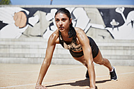 Fit woman doing pushups outdoors - SUF00189