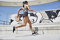 Fit woman running outdoors - SUF00195