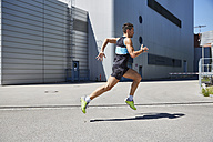 Fit man running along building - SUF00207