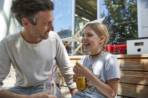 Happy father and daughter with drinks at an outdoor cafe - SUF00210