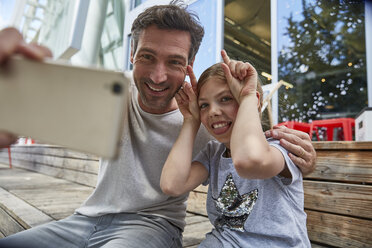 Father and playful daughter taking a selfie at an outdoor cafe - SUF00213