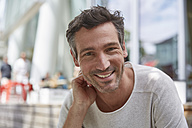 Portrait of smiling man at an outdoor cafe - SUF00216