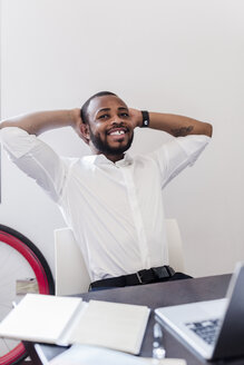 Relaxed businessman at desk leaning back - GIOF02915