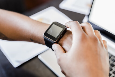Close-up of businessman wearing smartwatch - GIOF02918