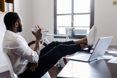 Relaxed man in home office with feet on desk - GIOF02924