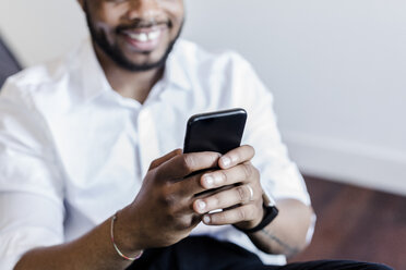 Close-up of smiling man using cell phone - GIOF02927