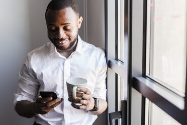 Smiling man holding cell phone and cup of coffee at the window - GIOF02933