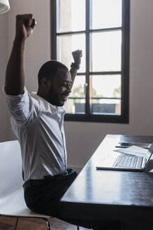 Happy businessman with laptop at desk raising his arms - GIOF02939
