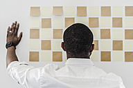 Man looking at adhesive notes on wall in office - GIOF02942