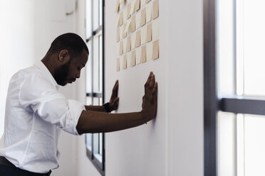 Man leaning against wall  with adhesive notes in office - GIOF02945