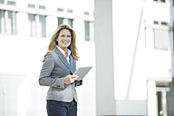 Happy businesswoman holding tablet outdoors - MAEF12271