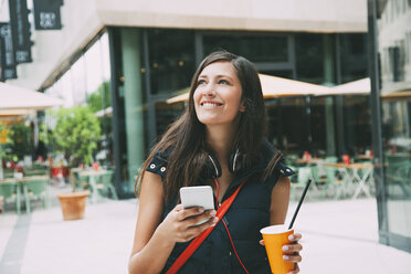 Portrait of smiling young woman with cell phone and takeaway drink in the city - CHAF01910