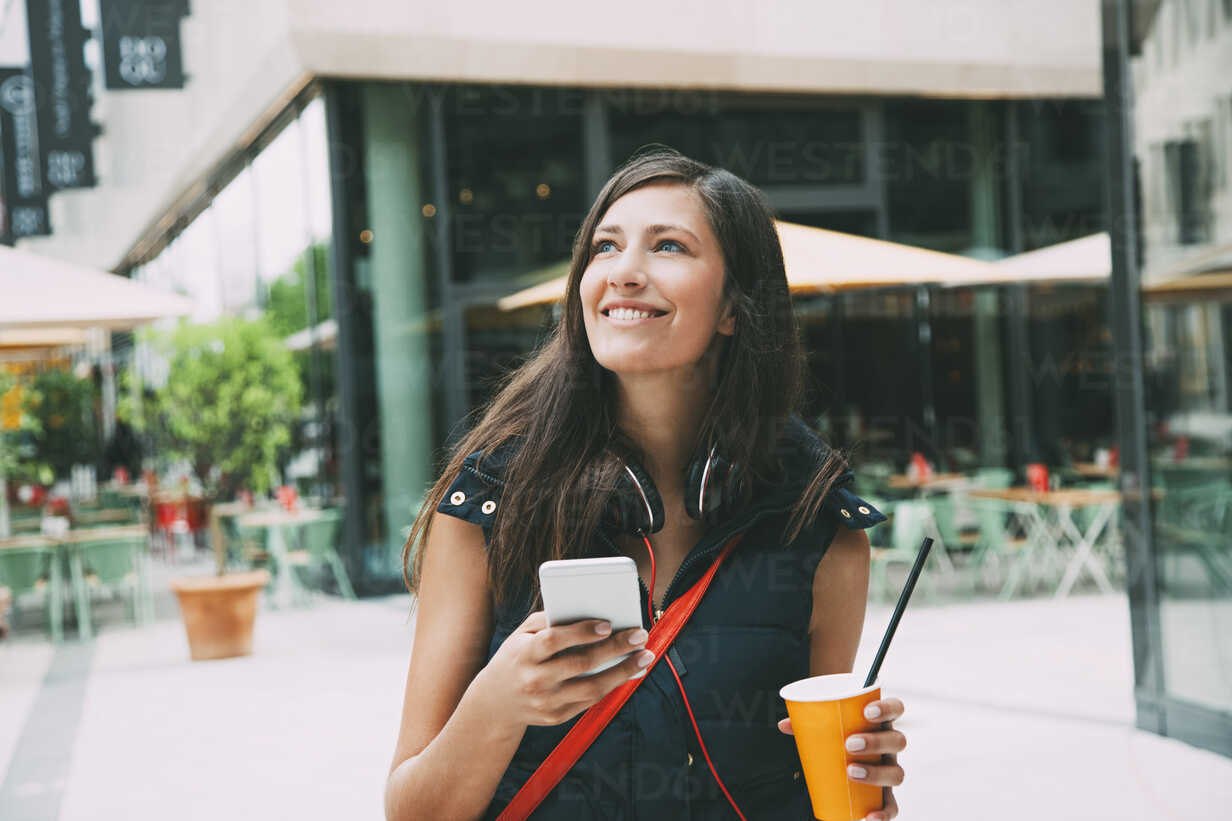 Portrait of smiling young woman with cell phone and takeaway drink in the city - CHAF01910 - Chris Adams/Westend61
