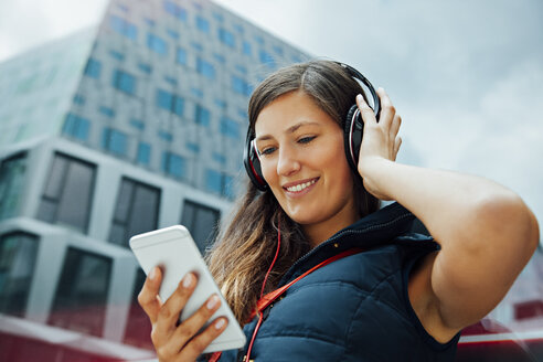 Smiling young woman with headphones and cell phone in the city - CHAF01913