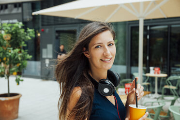 Portrait of smiling young woman with headphones and takeaway drink in the city - CHAF01916