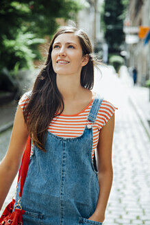 Smiling young woman in the city looking around - CHAF01919