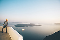 Greece, Santorini, Fira, man on holidays enjoying the sunset over the sea - GEMF01736