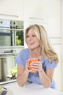 Happy woman at home with cup of coffee - MAEF12283