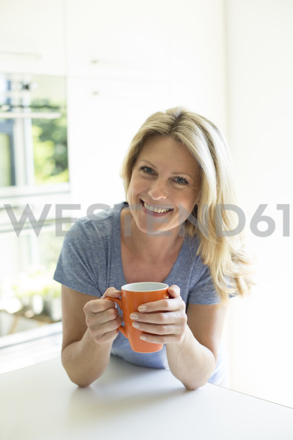 Portrait of smiling woman at home with cup of coffee - MAEF12286 - Roman Märzinger/Westend61