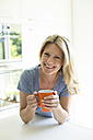 Portrait of smiling woman at home with cup of coffee - MAEF12286