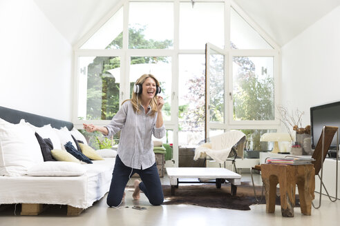 Excited woman at home listening to music - MAEF12301