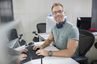 Employee at his desk smiling - ZEF14073