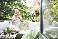 Mature woman sitting on balcony, eating water melon - MAEF12315