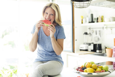 Mature woman sitting in kitchen, eating water melon - MAEF12318