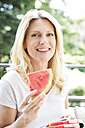 Mature woman sitting on balcony, eating water melon, portrait - MAEF12321
