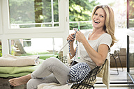 Mature woman sitting in living room, knitting - MAEF12327