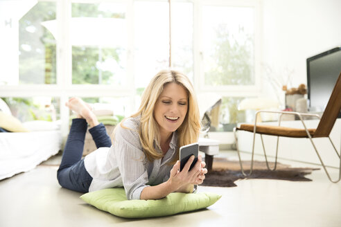 Mature woman lying on floor, using smartphone - MAEF12333